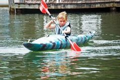 Boy in Kayak/Concentration. A young boy deep in thought as he paddles the kayak royalty free stock photos