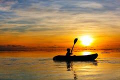 Boy kayaking at sunset Stock Image