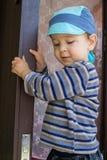Boy keeps door. Little boy keeps hands with a door yard Stock Photo
