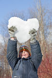 Boy keeps in hands hearts from snow over head. In winter in wood Stock Images