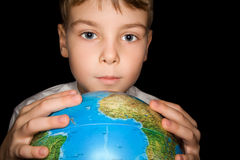 Boy keeps in hands over globe of world isolated. On black background Stock Image