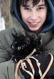 Boy keeps a snow black cat in his hands Stock Photos