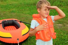 Boy keeps watch and inflatable boat on lawn. Summer stock images