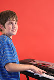 Boy on keyboard left vertical. Photo of a boy on keyboard left vertical Stock Photos