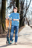 Boy with kick scooter Royalty Free Stock Image
