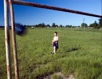 Boy kicking ball Stock Photography