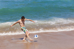 Boy Kicking Ball Beach royalty free stock photography