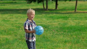 Boy kicking ball in the field stock footage