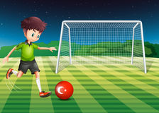 A boy kicking the ball at the field with the flag of Turkey Royalty Free Stock Image