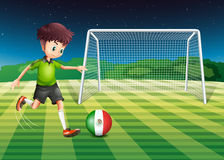 A boy kicking the ball with the flag of Mexico Stock Photography