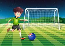 Boy kicking the ball with the flag of New Zealand Royalty Free Stock Image