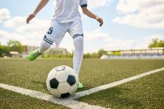 Boy Kicking Ball on Football Field royalty free stock photo