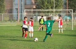 Boy kicking a ball Stock Photos