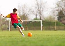 Boy kicking a ball at goal Royalty Free Stock Photography