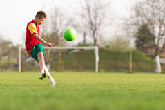 Boy kicking a ball at goal Stock Photos