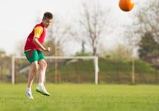 Boy kicking a ball at goal Stock Images