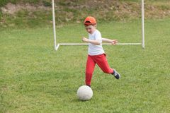 Little boy kicking ball in the park. playing soccer football in the park. Sports for exercise and activity. Boy kicking ball in the park. playing soccer royalty free stock image