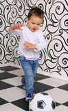 Boy kicking ball. In the studio in a corner with a black and white pattern Stock Photos