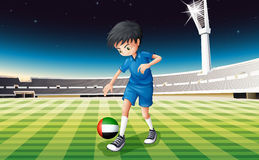 A boy kicking ball with United Arab Emirates flag Stock Photo