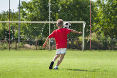 Boy kicking footbal Stock Photos