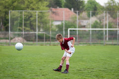Boy kicking football Stock Photo