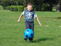 Boy kicking football stock image