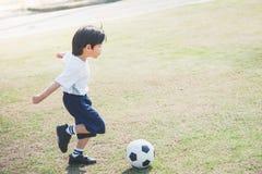 Boy kicking football Stock Images