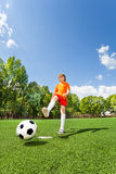 Boy kicking football with one leg Royalty Free Stock Photography