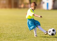 Boy kicking football on the sports field Royalty Free Stock Photo
