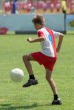 Boy kicking football Stock Photos