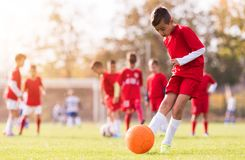 Boy kicking football on the sports field. During soccer match stock image