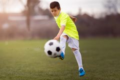 Boy kicking football on the sports field. During soccer match Royalty Free Stock Photography