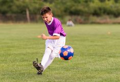 Boy kicking football on the sports field Stock Image