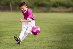 Boy kicking football on the sports field. During soccer match Royalty Free Stock Images