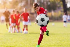 Boy kicking football on the sports field. During soccer match royalty free stock photos