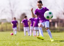 Boy kicking football on the sports field Royalty Free Stock Photography