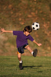 Boy kicking soccer ball. Boy kicking a soccer ball in the early evening sun stock photography