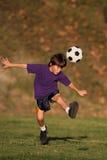 Boy kicking soccer ball. Boy kicking a soccer ball in the early evening sun Stock Photography