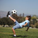 Boy kicking soccer ball. A young boy performs a soccer bicycle kick in a park Stock Image