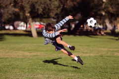 Boy kicking soccer ball Stock Photo