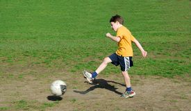 Boy kicking soccer ball Royalty Free Stock Photos