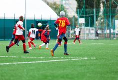 Boy is kicking soccer ball. Boy is running after the ball on green grass. footballer in white and red shirt. boys dribbling. stock image