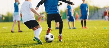 Boy kicking soccer ball. Close up action of boys soccer teams, aged 8-10, playing a football match. Sports school competition between children royalty free stock photos
