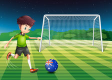 A boy kicking the soccer ball at the field with the flag of Aust Royalty Free Stock Images