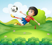A boy kicking the soccer ball at the hilltop Royalty Free Stock Image