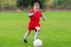 Boy kicking soccer ball. On sports field royalty free stock image