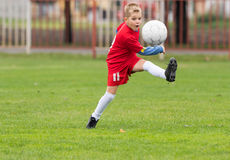 Boy kicking soccer ball Stock Images