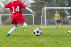 Boy kicking soccer ball. On sports field royalty free stock photos