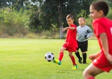 Boy kicking soccer ball. On sports field royalty free stock photography