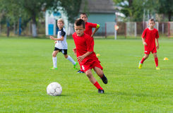Boy kicking soccer ball. On sports field royalty free stock images